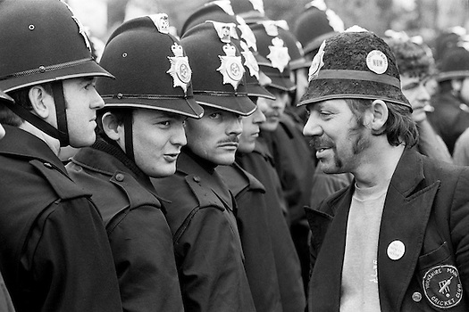 Picket wearing a joke police helmet talking to Police at Orgreave 1984-85 miners strike © Martin Jenkinson tel 0114 258 6808 mobile 07831 189363 email martin@pressphotos.co.uk NUJ recommended terms & conditions apply. Copyright Designs & Patents Act 1988. Moral rights asserted credit required. No part of this photo to be stored, reproduced, manipulated or transmitted by any means without prior written permission.